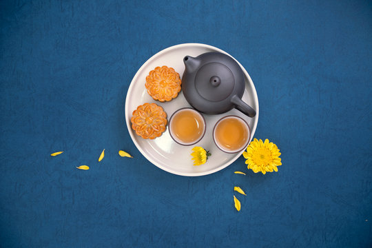 Minimal simplicity layout moon cakes on blue background for Mid-Autumn Festival, creative food design concept, top view, flat lay, copy space.