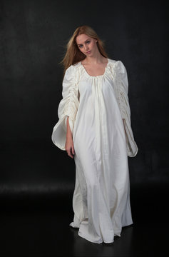 full length portrait of blonde girl wearing long white flowing robe. standing pose against a black studio background.