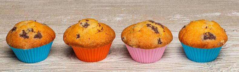 Obraz Muffinki w kolorowych foremkach. Słodkie babeczki na drewnianym blacie. - fototapety do salonu