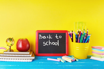 black chalk frame, chalks and school supplies on a blue background Wall mural