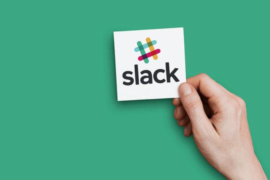 LONDON, UK - October 30th 2018: Hand holding a Slack logo. Slack is a cloud based collaboration tool.