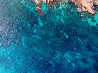 Mediterranean Sea with turquoise water beats on coast of island of Malta. Aerial top view