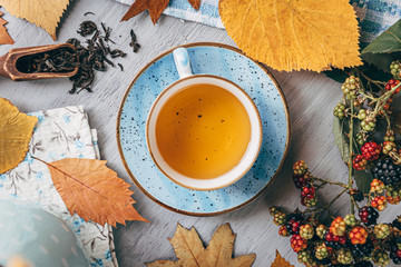 autumn warming tea on a wooden table with autumn tree leaves lying nearby