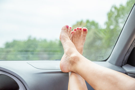 bare feet of a woman resting on the car dashboard