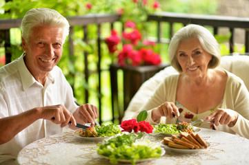 Portrait of happy senior couple having diner Fototapete