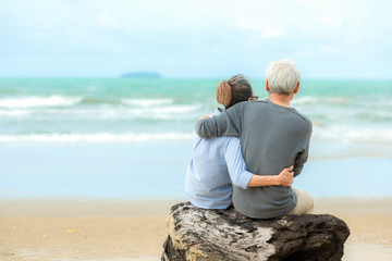 Asian Lifestyle senior couple hug and sitting on the beach happy in love romantic and relax time.  Tourism elderly family travel leisure and activity after retirement in vacations and summer..