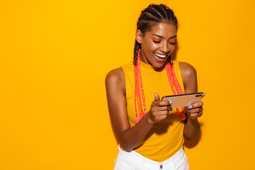 Image of beautiful african american woman with afro braids smiling and holding smartphone