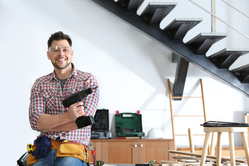 Handsome working man with electric screwdriver indoors, space for text. Home repair