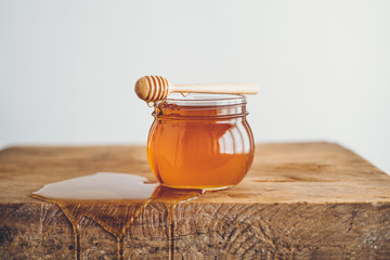 Honey in a glass and Honey scoop White background