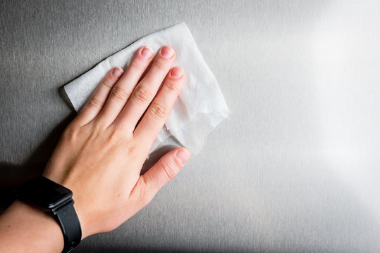 Female hand wiping metal surface with white rag.