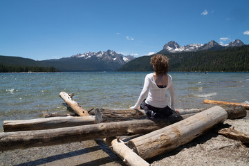 Adult woman (30-35 years) sits on a pile of logs on the shoreline of Redfish Lake in Stanley Idaho in the Sawtooth Mountains in summer