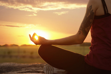 Young woman practicing zen yoga at sunrise outdoors, closeup