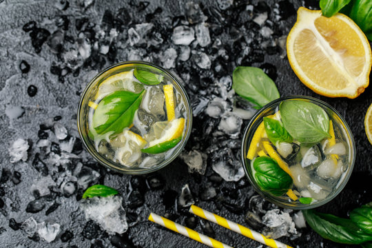 Summer basil lemonade on grey background. Fresh summer cocktail with basil, lemon and ice cubes. Homemade fresh lemonade with lemon and basil. Food and drink concept