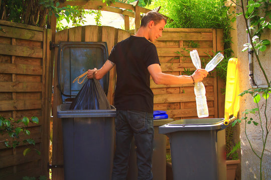 View on profil of one person performing a selective sorting of household waste in recycling bins. Man putting plastic bottles in a yellow container and garbage in a bag in a green container.