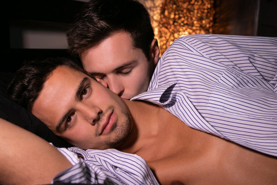 Male gay couple in bed with one man looking at camera and the other kissing his neck