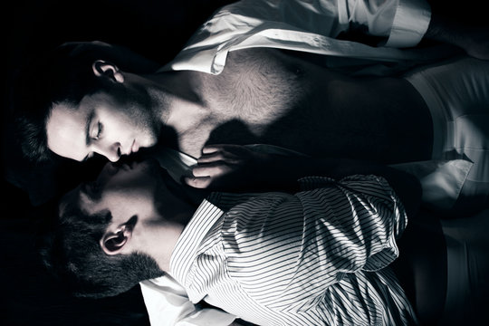 Gay male couple lying in bed about to kiss each other