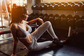 Young woman with earphones listening to music after hard workout in gym. Relax concept. Strength training and Body build up theme. Warm and cool tonePretty girl scrolling in her mobile phone. Close up