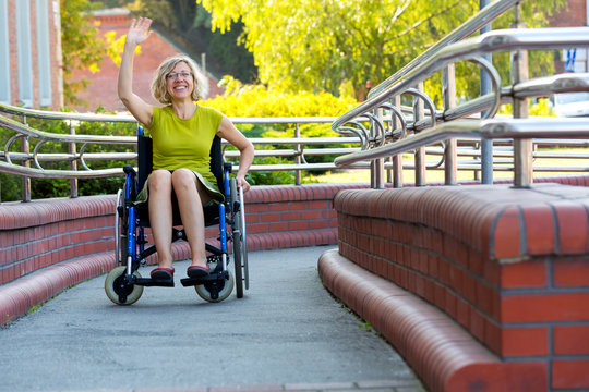 woman on wheelchair waving with a hand