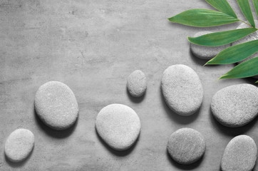 Flat lay composition with spa stones, palm leaves on grey background.