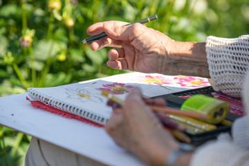 Seniorin beim Zeichnen im botanischen Garten