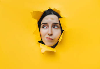 A young girl expresses a toothache with her facial expressions. The concept of spying, skepticism and distrust. Yellow torn paper, copy space.