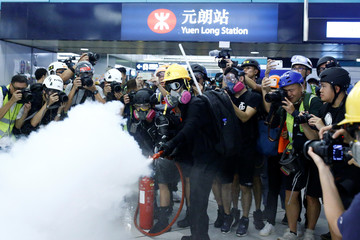 Journalists take pictures of a protester using a fire extinguisher inside Yuen Long MTR station in Yuen Long, New Territories, Hong Kong