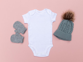 Blank baby bodysuit babygrow surrounded by a winter hat and gloves on a pink background