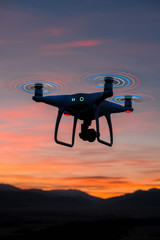 quadrocopter with glowing blades flies and shoot the sunset and nature