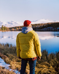 a young guy in a yellow jacket is standing on the shore of a lake. winter mountain landscape