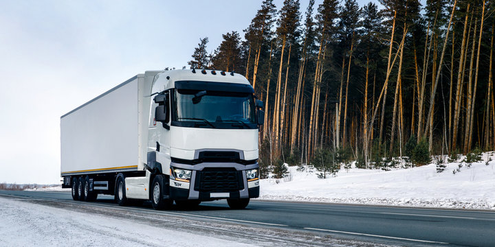 The truck rides on a winter snowy road in the forest.