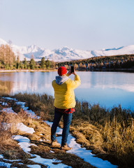 young guy in a yellow jacket takes pictures of a winter mountain landscape