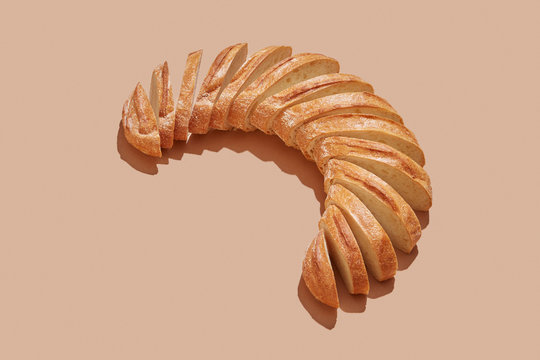 Sliced white bread, homemade in the form of semicircle on a pastel beige background with copy space.
