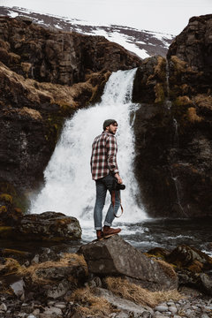 Tourist with camera against waterfall