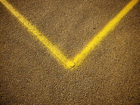 V shaped yellow line on the asphalt, abstract
