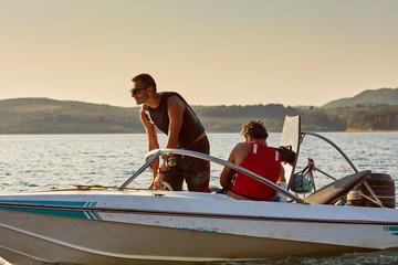men on a motor boat preparing for jet ski