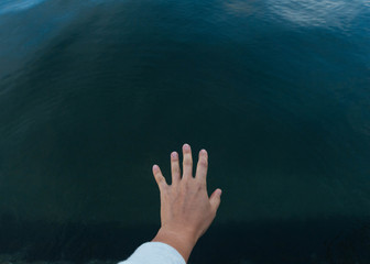 Stock image shot of hand reaching for the ocean
