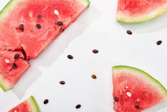 top view of juicy watermelon slices with seeds on white background