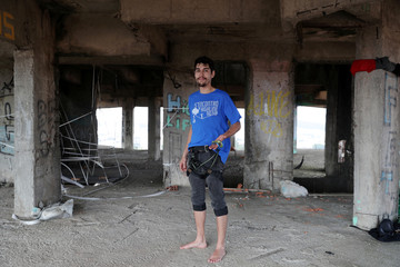 Samuel Helfenstens, 26, poses for a picture with his highline equipment in an unfinished building in Sao Bernardo do Campo