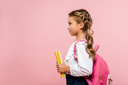side view of happy kid holding books while standing with backpack isolated on pink