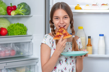 Hungry beautiful young teen girl eats slice of pizza while standing near open fridge in kitchen at...