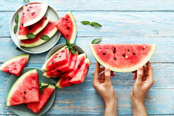 Fresh red watermelon slice in female hands on an blue rustic wood background with copy space.  Top view. Summertime concept. Watermelon slice and mint on the background.
