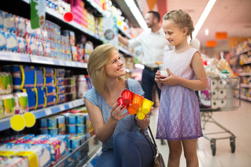 Portrait of  woman and girl holding package with yogurt in grocery shop