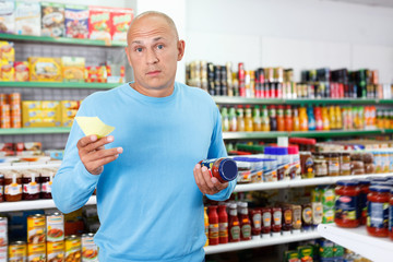 Focused man choosing fresh products during shopping at food store