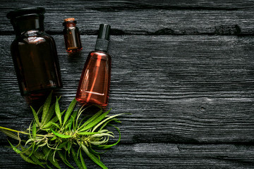 Cannabis cbd oil in bottle and green leaves on a black wooden table flat lay background.