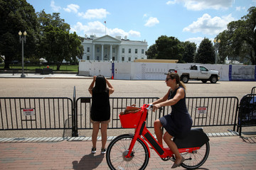 Guests take photos near the White House during construction on the perimeter fence by National Park Service and United States Secret Service at the White House in Washington D.C.