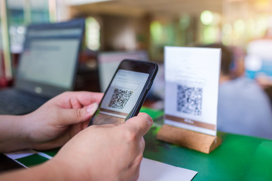 Closeup of a hand holding phone and scanning QR code with blurry cashier at counter service. Man hands paying with QR code. Customer hands making payment through smart phone and scan code.