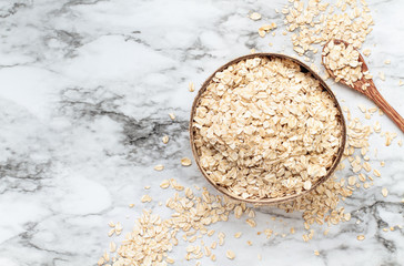 Healthy raw uncooked quick oat flakes in a wooden bowl over a marble table background. Shot from top view.