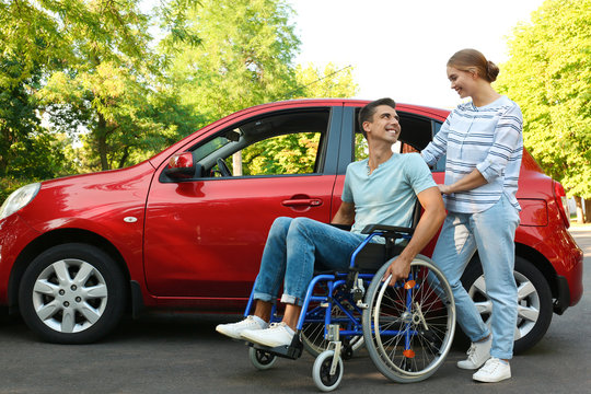 Young woman with disabled man in wheelchair near car outdoors