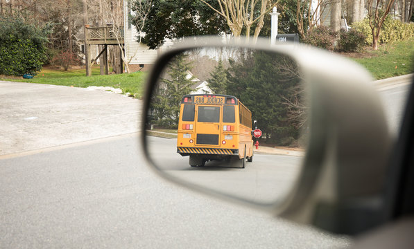 Bus stop in the side mirror of a car