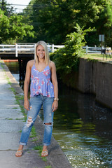 Beautiful young blonde woman poses outside in denim and print tank-top - near creek or canal